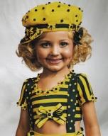 """Jasmine prefere ser chamada de """"Jazzy"""". Vive numa mansão com seus pais e 3 irmãos e seu quarto está cheio de coroas e outros objetos que ganhou em """"concursos pra crianças"""". Com apenas 4 anos, já participou em milhares dessas competições, que podem custar também milhares de dólares aos pais. Jazzy gosta de ser tratada como uma princesa e ter seu cabelo e unhas arrumados, boas roupas e maquiagem impecável. Vive no Kentucky, EUA."""